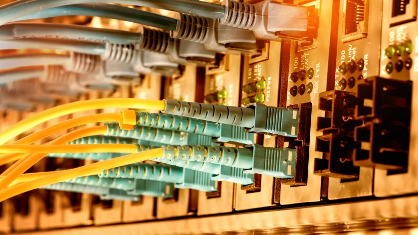 Bank of fiber optic cables plugged in to receptacles.