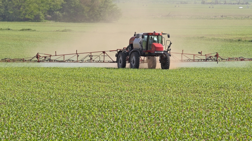 Agricultural vehicle spraying chemicals on a corn field